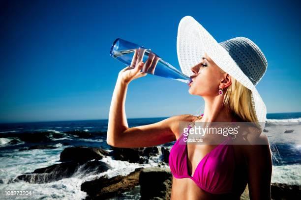 若い女性のボトル入り飲料水の上海浜