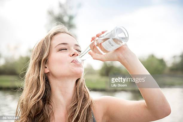 Young woman drinking water from bottle, outdoors