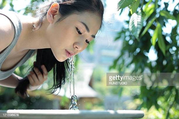 young woman drinking water outside