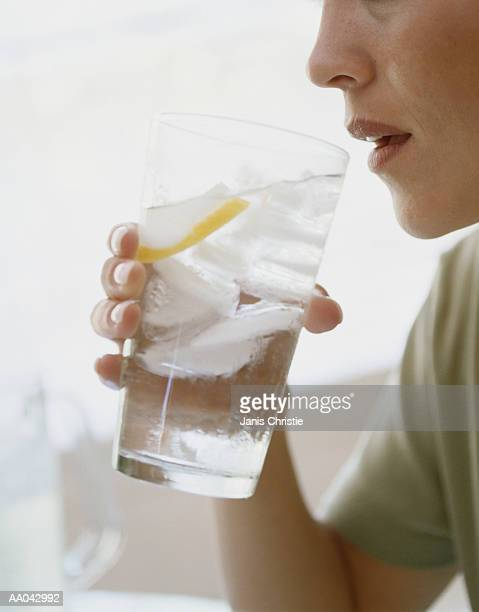 Young woman drinking water, side view, close-up