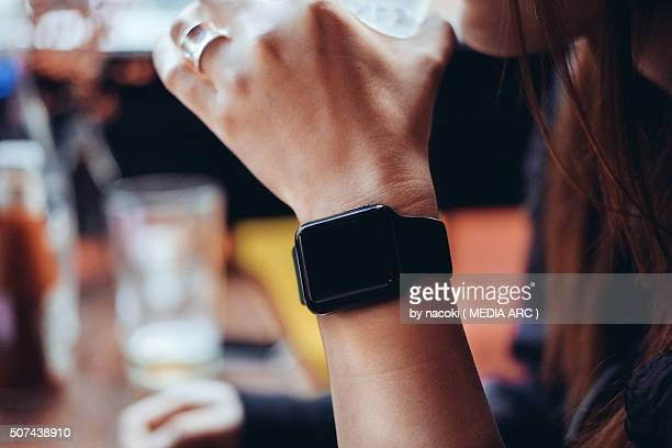 Young woman drinking with smart watch