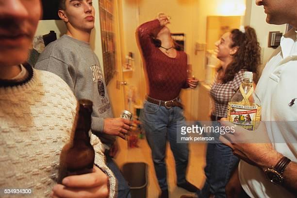 A young woman drinks a shot of alcohol at a party at Manzanita Residence Hall Dormitory at Arizona State University