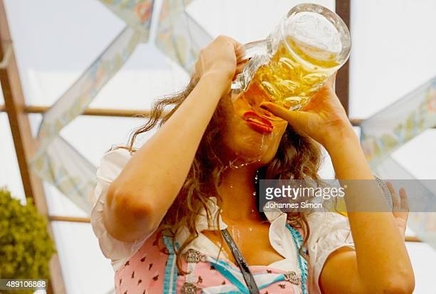 A young woman drinks beer at Hofbraeuhaus beer tent on the opening day of the 2015 Oktoberfest on September 19 2015 in Munich Germany The 182nd...