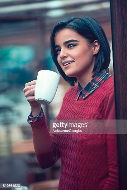 Young Woman Drinks Coffe and Looking Through Window in Cafe