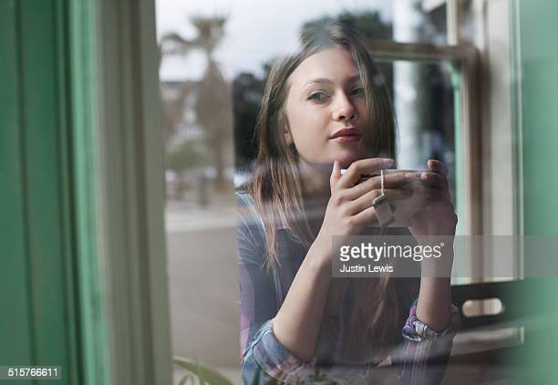 Young woman drinks tea at cafe, reflections