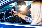Young happy smiling woman driver taking a selfie photo on a smartphone in her modern luxury car