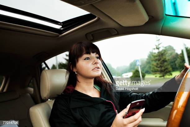 Young woman drives her car while text messaging on her mobile phone in Tallinn Estonia Estonia gained independence from Russia in 1991 and freed from...