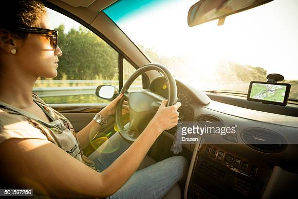 Young woman driving car and speeding on highway in summer