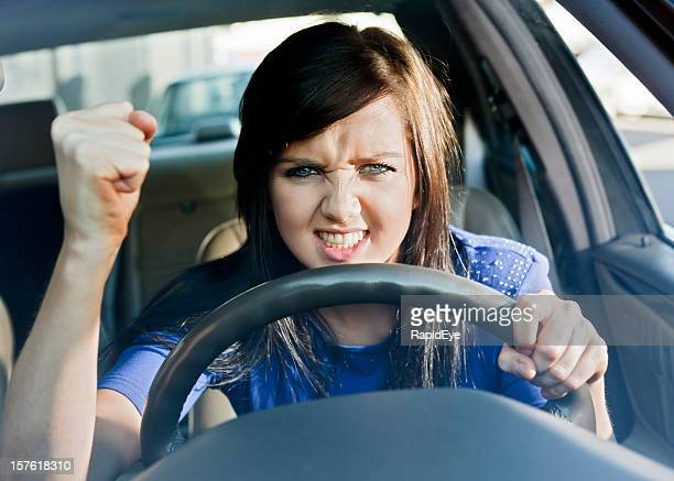 Young woman driving car shakes her fist in frustrated fury