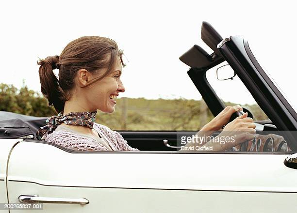 Young woman driving car, smiling, side view