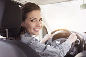 Young beautiful woman driving her car, she is holding the steering wheel and smiling at camera