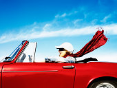 Young woman driving red convertible car, side view