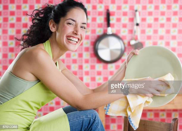 Young woman drying a plate