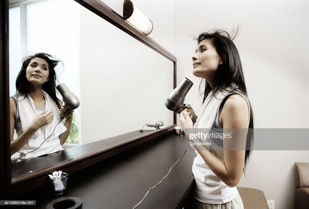Young woman drying hair in front of large mirror : Stock Photo