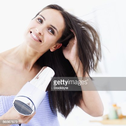 young woman drying her hair with a hair dryer