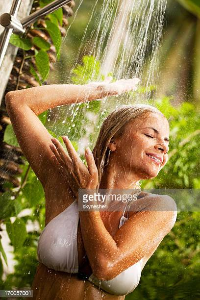 Young woman during showering outdoor.