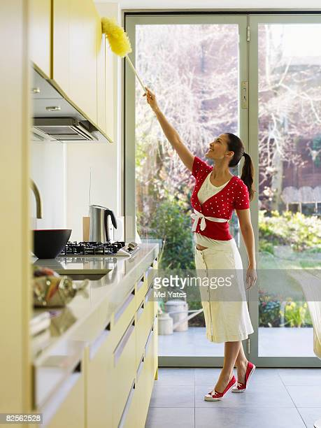 Young woman dusting in kitchen