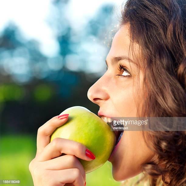 Joven mujer comer manzana verde