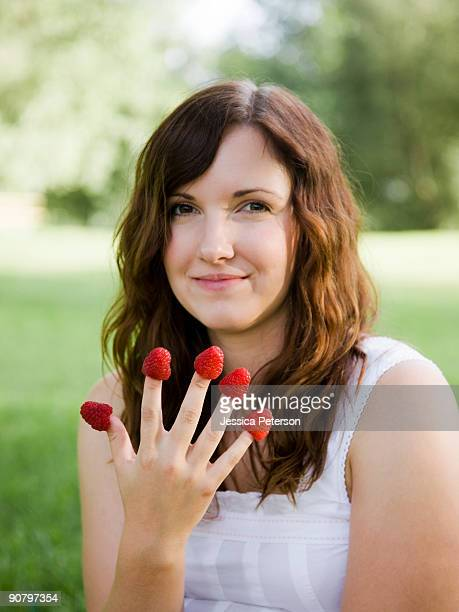 young woman eating a berry from each finger