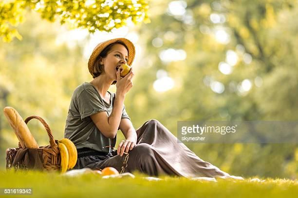 Mujer joven comiendo una manzana en día de campo durante la primavera.