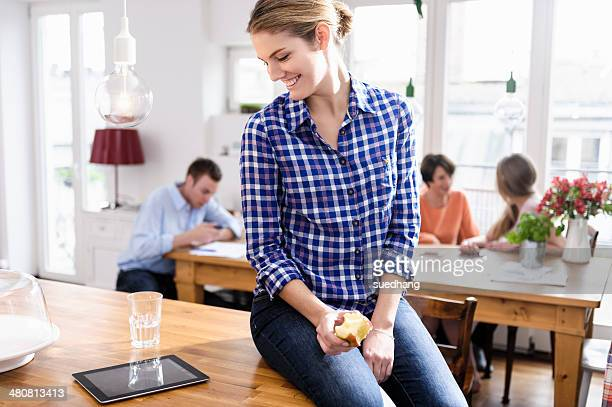 Young woman eating apple looking at tablet screen smiling, people in background