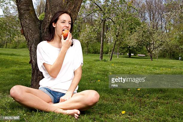 Young woman eating apple on meadow