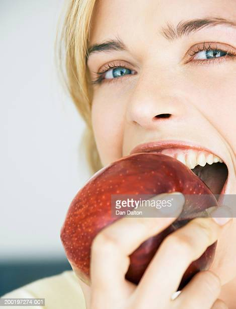 Young woman eating apple, portrait, close-up