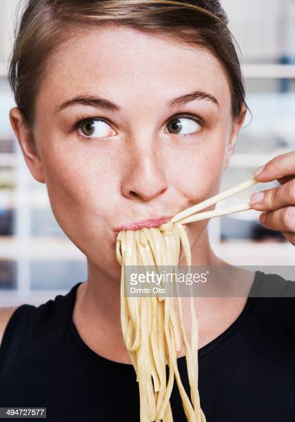 Young woman eating Asian noodles, close-up