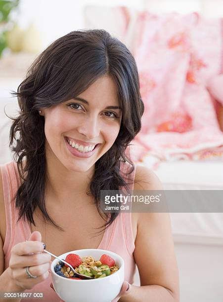 Young woman eating bowl of granola and fruit, close-up portrait.