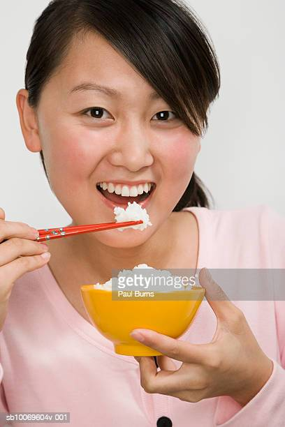 Young woman eating bowl of rice with chopsticks, portrait
