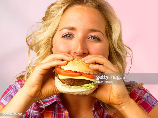 Young woman eating burger, close-up, portrait
