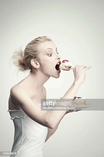 Young woman eating cake, side view, portrait