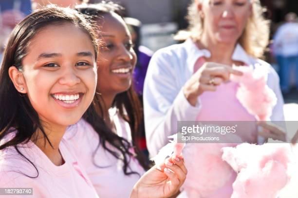Junge Frau Essen Zuckerwatte im Cancer Awareness zu Fuß