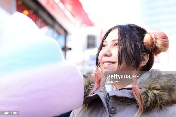 Young woman eating cotton candy