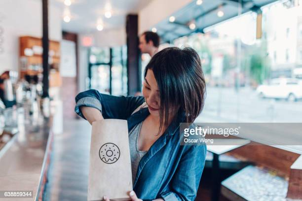 Young woman eating donut in a cafe