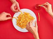 Young woman and man eating french fries potato with ketchup in a restaurant, having her lunch break. Close up
