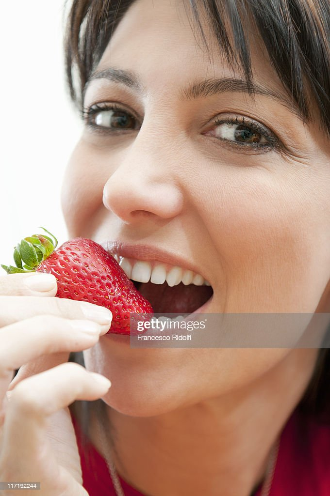 Young woman eating fresh strawberry : Stock Photo