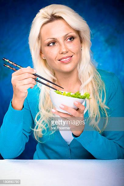 Young woman eating from bowl with chopsticks