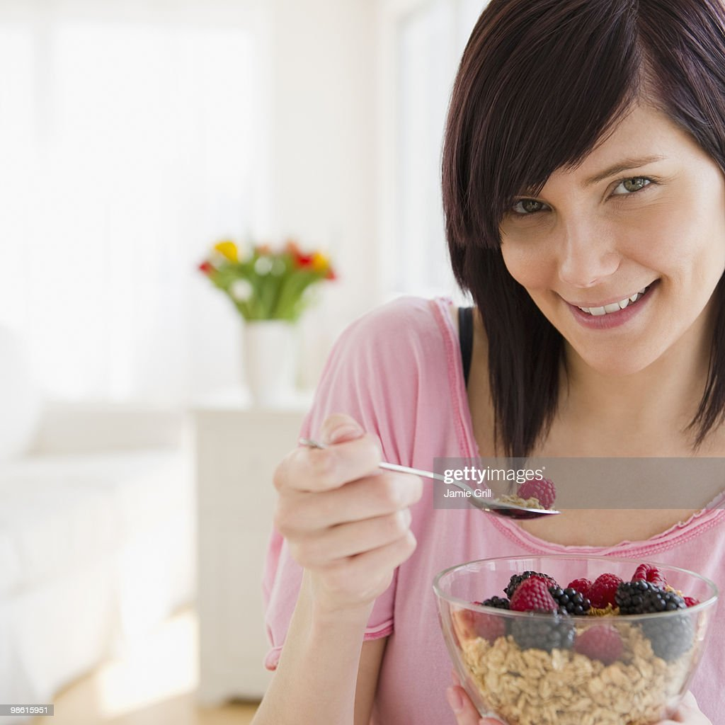 Young woman eating granola with fresh fruit : Stock Photo