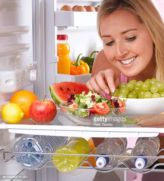 Young woman eating grapes from fridge stocked with healthy food
