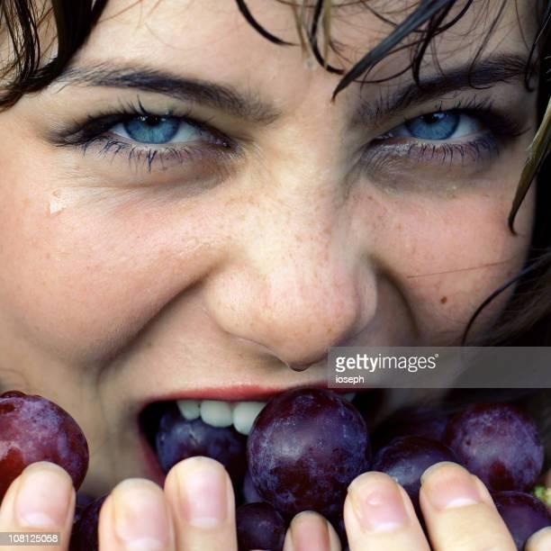 Jeune femme manger le raisin