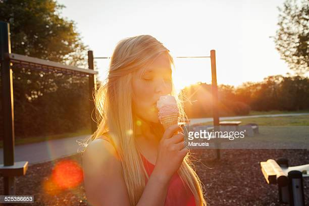 Young woman eating ice cream cone in park at sunset