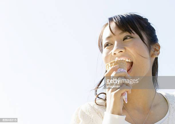 A young woman eating ice cream cone