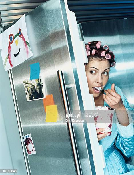 Young woman eating ice-cream by refrigerator