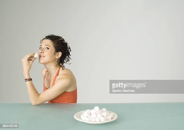 Young woman eating marshmallows