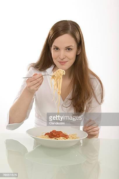 Young woman eating noodles, portrait