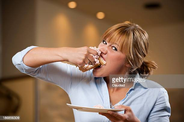 Young woman eating piece of cake with both hands