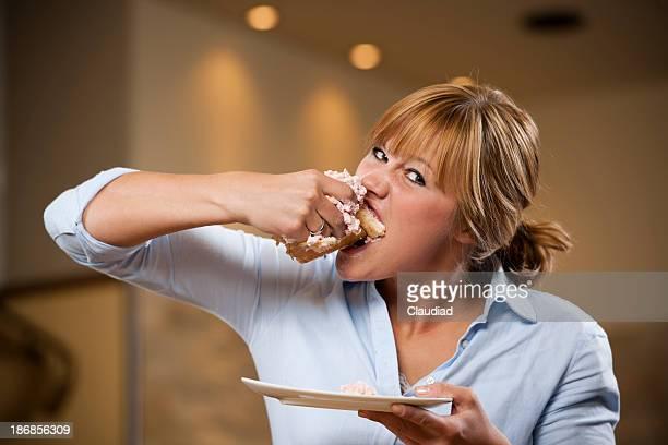 Junge Frau Essen ein Stück Kuchen mit beiden Händen