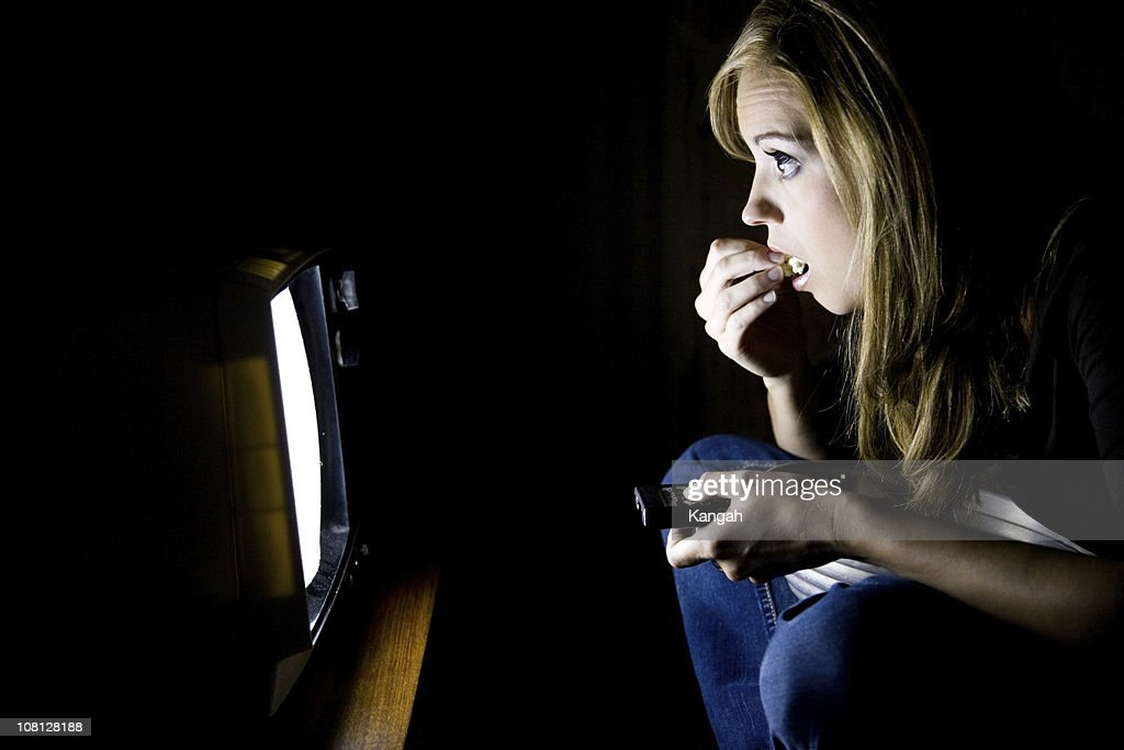 Young Woman Eating Popcorn in Front of television