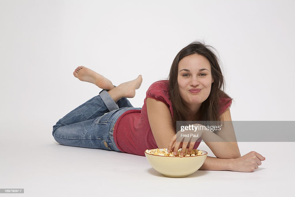 Young woman eating popcorn : Stock Photo